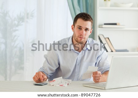 Young businessman checking bills in his home office - stock photo