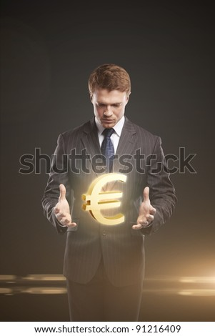 Young  businessman chooses a Gold Euro Sign. On a black background - stock photo