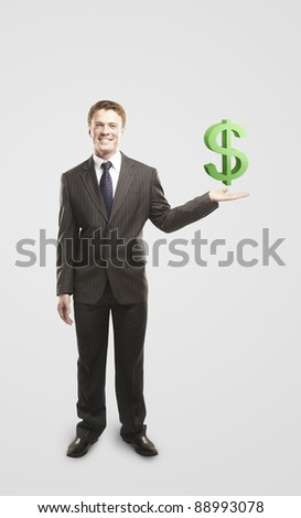 Young  businessman chooses a green US dollar sign.On a gray background - stock photo