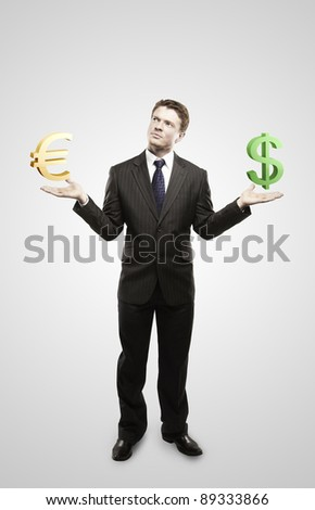 Young  businessman chooses euro or dollar signs.On a gray background