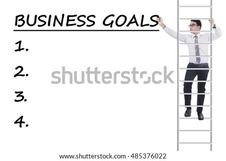 Young businessman climbing a ladder and write business goals, isolated on white background