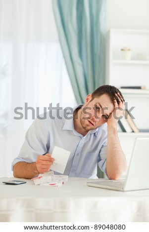 Young businessman concerned about bills - stock photo