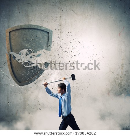 Young businessman crashing stone shield with hammer - stock photo