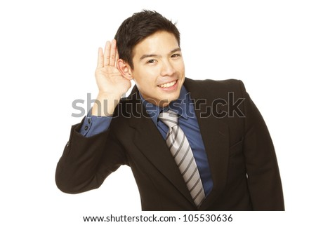 Young businessman cupping his ear and trying to listen - stock photo