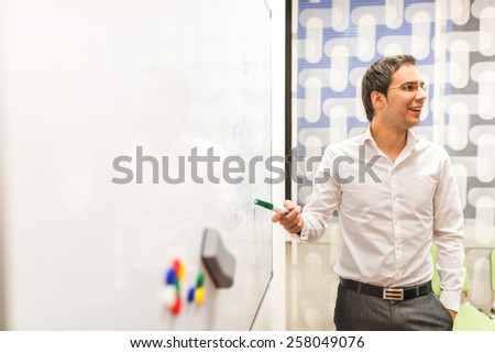 Young Businessman Discussing Business Plans While Pointing at the White Board and Facing the Listeners at Right of the Frame. - stock photo