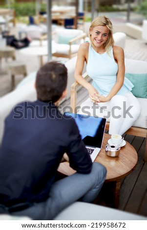 Young businessman discussing plan with female colleague,businesspeople having work meeting outdoors the office, young partners having discussion while one of colleagues working with laptop pc computer - stock photo
