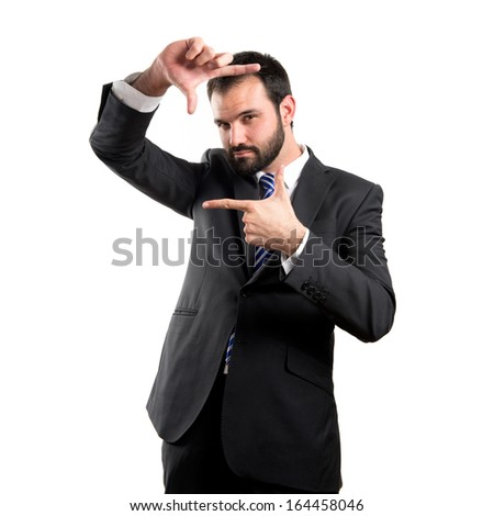 Young businessman doing a frame sign over white background