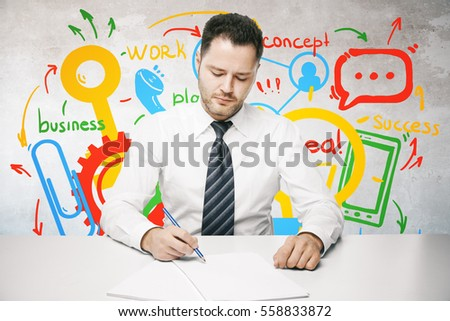 Young businessman doing paperwork at workplace with colorful business sketch. Success concept