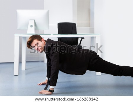Young Businessman Doing Pushups At His Workplace - stock photo