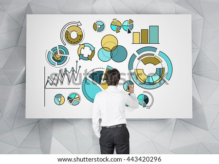 Young businessman drawing business pie charts on whiteboard hanging on abstract polygon patterned wall - stock photo