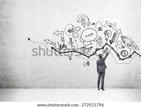 young businessman drawing many different business icons on a concrete wall over a graph. Back view. Concept of business development. - stock photo