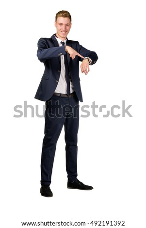 Young businessman dressed in a suit points to at watch isolated on white