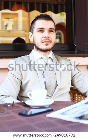 Young businessman drinking a cup of coffee while sitting at a coffee shop terrace table - stock photo
