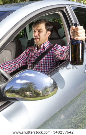 Young businessman drinking alcohol while driving his car - stock photo