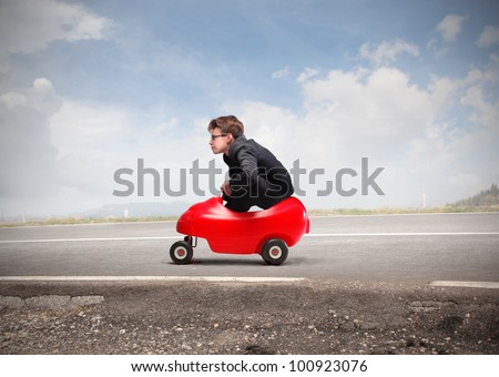 Young businessman driving a toy car on a road - stock photo