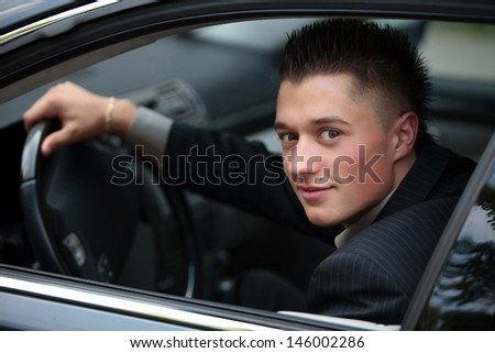 young businessman driving car - stock photo