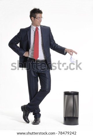 Young businessman dropping a paper in a waste basket. Young businessman dropping a paper in a trash bin. - stock photo
