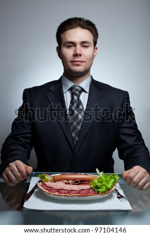 Young businessman eating. Rich meat menu. - stock photo