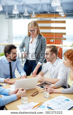 Young businessman explaining his idea to colleagues at meeting in office - stock photo
