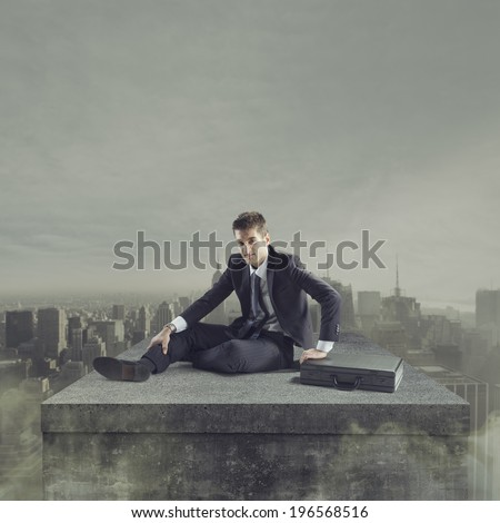 Young businessman falling to the ground with post apocalyptic cityscape on background. - stock photo