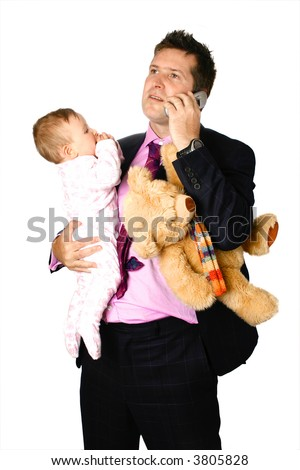 Young businessman father holding his baby and teddy under one arm while making phone call, concept of family life and work pressure. - stock photo