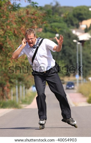 Young businessman go to work with a roller skate  and makes a phone-call very angrily - stock photo