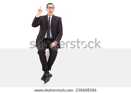 Young businessman has an idea seated on a panel isolated on white background - stock photo