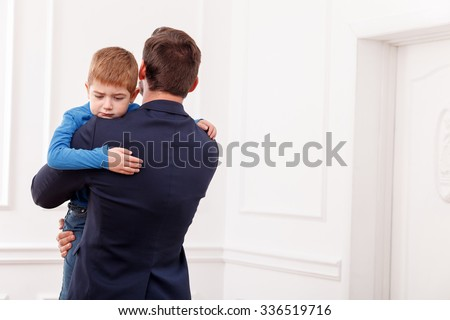 Young businessman has to go to work. He is holding his son and embracing. The boy is crying with despair. Copy space in right side - stock photo
