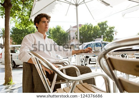 Young businessman having a coffee while sitting outdoors at a coffee shop terrace table in the shade on a sunny day.