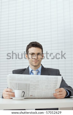 Young businessman having coffee break, sitting at office desk and reading newspaper. Copy space. - stock photo