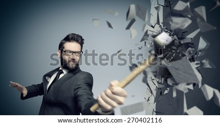 Young businessman hitting concrete wall with a hammer - stock photo