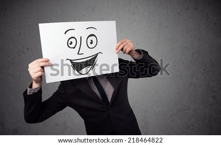 Young businessman holding a cardboard with a smiley face on it in front of his head - stock photo