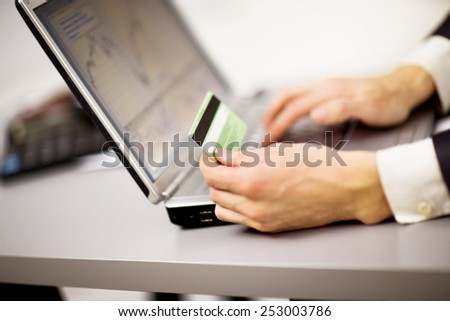 Young businessman holding a credit card and typing. On-line shopping on the internet using a laptop - stock photo