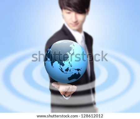 Young businessman holding a globe with asia map isolated on blue background, asian model