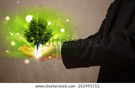 Young businessman holding a glowing tree in his hand - stock photo