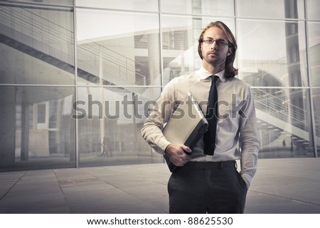 Young businessman holding a laptop with office building in the background