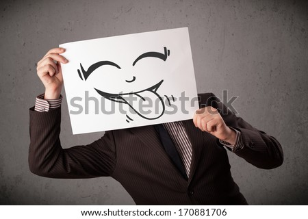 Young businessman holding a paper with funny smiley face on it in front of his head - stock photo