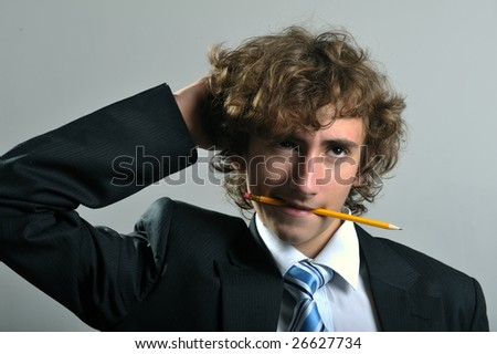 Young businessman holding a pencil in his mouth - stock photo