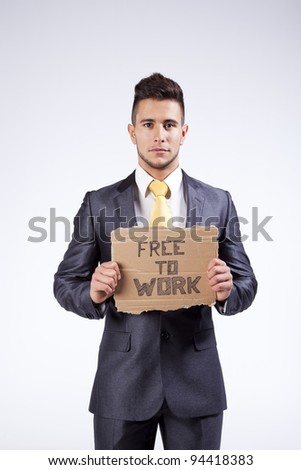 Young businessman holding a piece of cardboard saying Free to Work - stock photo