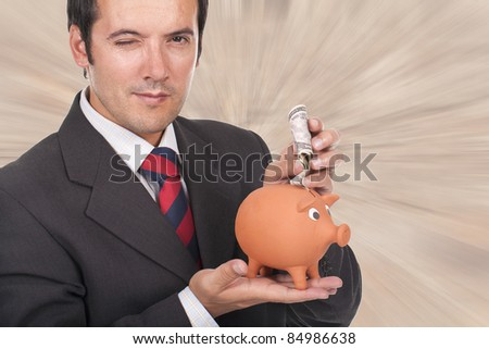 young businessman holding a piggy bank with dollar bills and blinking his eye - stock photo