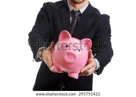 Young businessman holding a piggybank. - stock photo