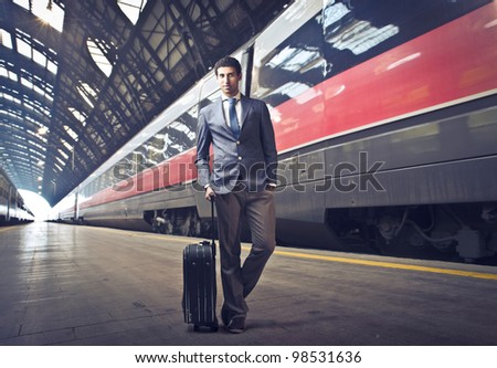 Young businessman holding a suitcase on the platform of a train station