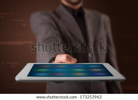 Young businessman holding a white modern tablet with blurry apps