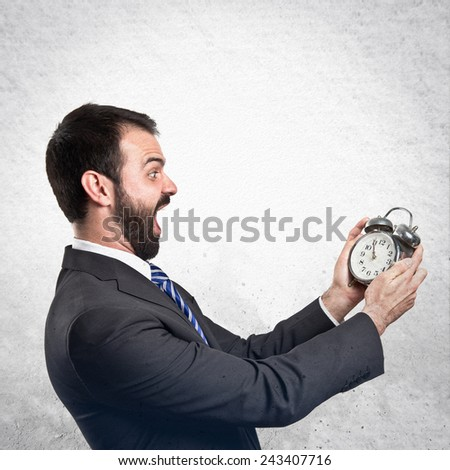 Young businessman holding an antique clock over textured background - stock photo