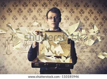 Young businessman holding an open briefcase with paper sheets flying away from it - stock photo