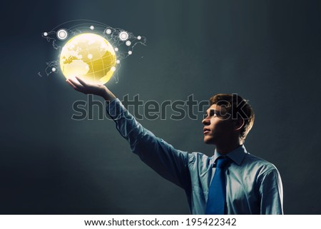 Young businessman holding digital globe in palm