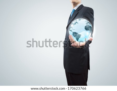 Young businessman holding Earth planet in palm - stock photo