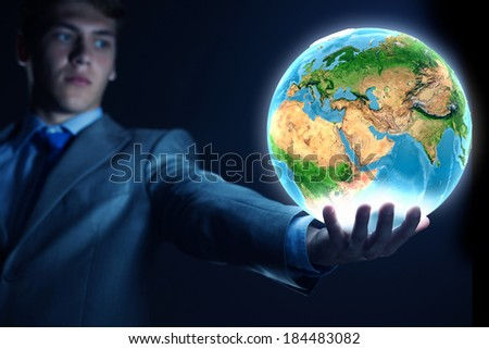 Young businessman holding Earth planet in palm. Elements of this image are furnished by NASA