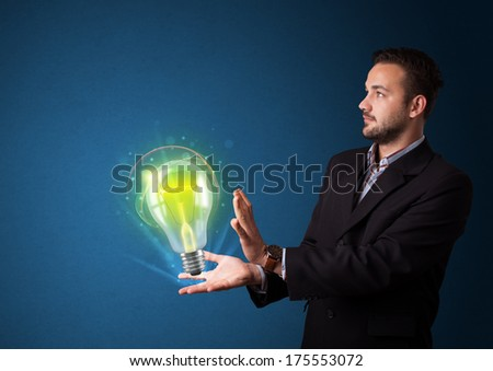 Young businessman holding glowing lightbulb in his hand