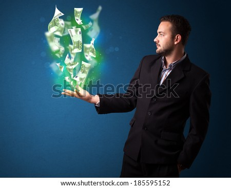 Young businessman holding glowing paper moneys in his hand - stock photo
